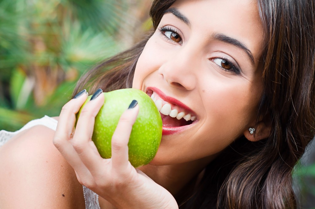 Portrait of a young woman's face eating an apple