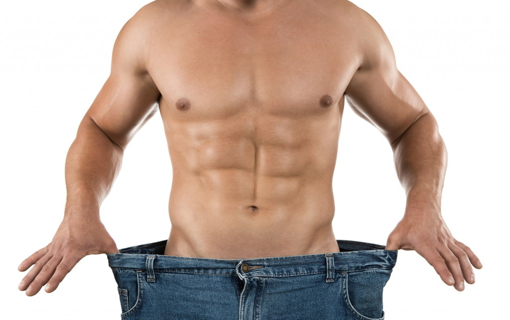 Weight loss, muscular man wearing too large jeans