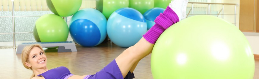 Young woman training with gymnastic ball in gym
