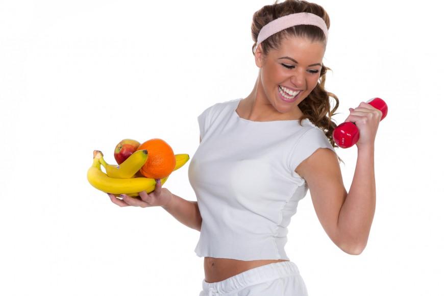 Lachende junge Frau mit Früchten und einer roten Hantel trainie