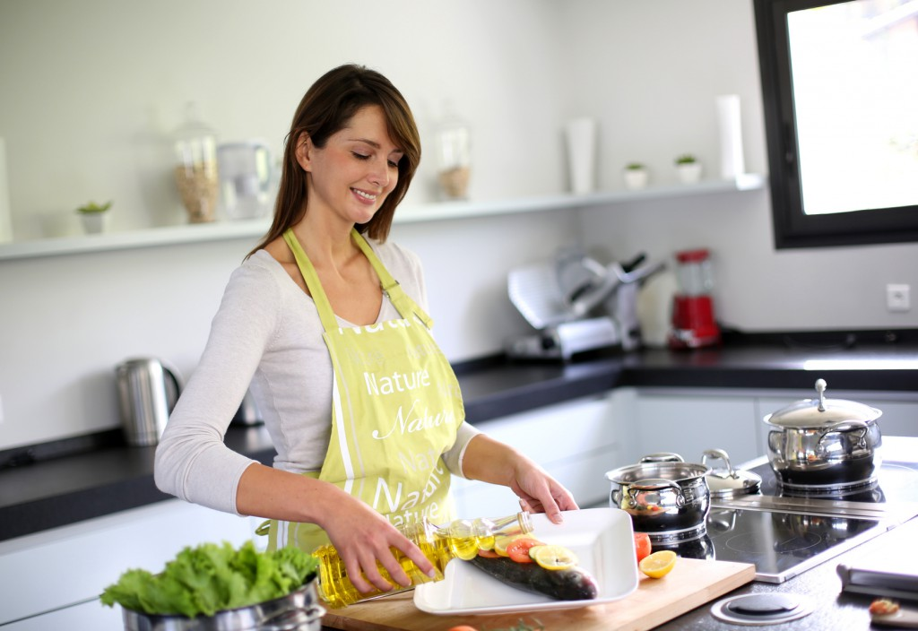 Woman in kitchen preparing fish dish