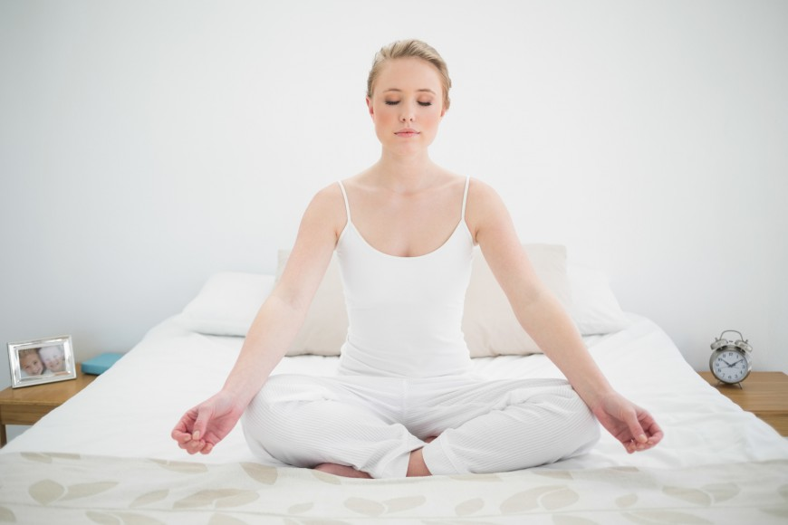 Natural pretty blonde meditating on bed with closed eyes in bright bedroom